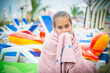 girl wrapped in a towel sitting on a lounger on the beach
