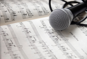 Microphone and cable lying on sheet of music