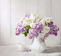 Lilac Bouquet  and  cup of coffee  against  wooden table.