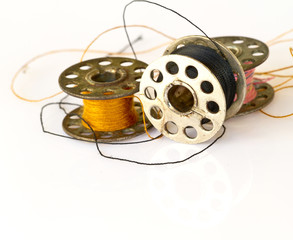 metal spool of thread or Sewing machine bobbins isolated on whit