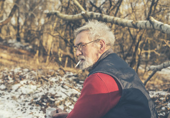 Elderly man smoking a cigarette outdoors in winter