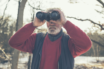 Elderly bearded man birdwatching in winter