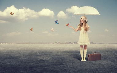 Young girl with white umbrella catches butterflies.