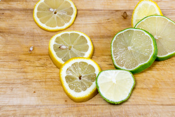Lime and lemon slices on wooden board