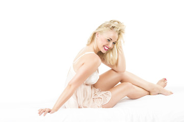 Happy Blond Girl Sitting on White Bed