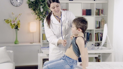 doctor visiting child with stethoscope in medical office
