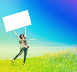 Happy girl flying with banner on sunny summer meadow.