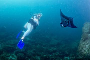 Blonde diver girl manta in the deep blue sea