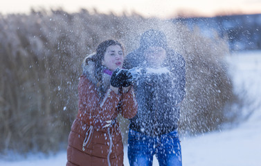 Girl with a guy blow away the snow