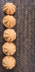 Kuih bahulu, a Malay sweet egg sponge cake on wicker mat.