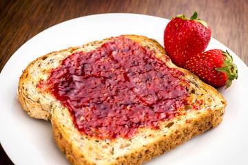 Macro closeup of delicious strawberry jam on whole wheat toast