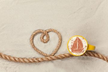Cup of coffee near heart shape rope