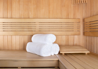 Traditional wooden sauna for relaxation with set of clean towels