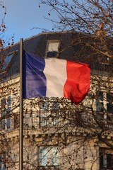 French flag over typical parisian building