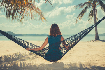 Woman sitting oin hammock on tropical beach