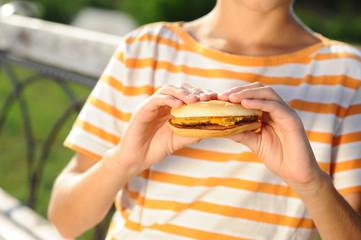 Boy holding burger closeup
