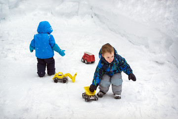 Two Boys Playing in Deep Snow with Trucks