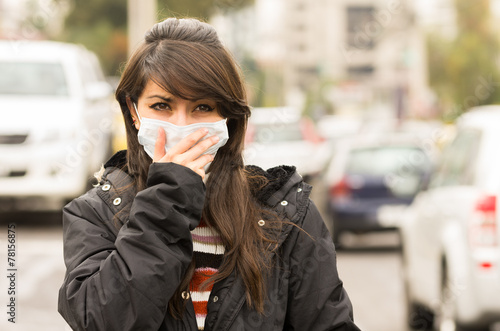 young girl walking wearing a mask in the city street concept of
