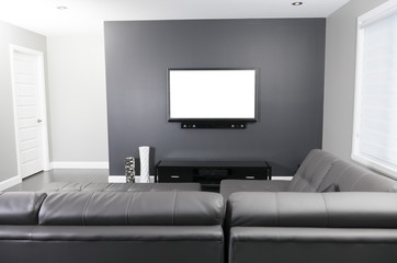 A gray and white living room with tv stand and sofa