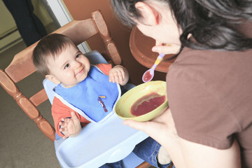 Mother feed baby in the kitchen with spoon.
