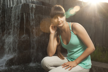 young beautiful girl near waterfall. bright sun and lens flare
