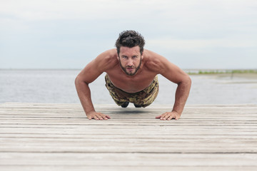 Shirtless Athletic Army in Camouflage Pants Doing Push Up Exerci