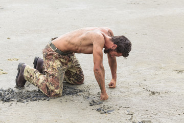 Muscled Shirtless Soldier in Camouflage Pants and Black Shoes Kn
