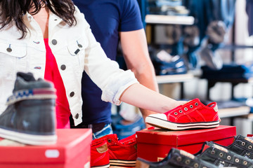 Woman buying sneakers shoes in shop