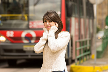 woman walking on the city street covering her ears concept of