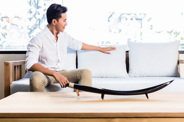 Asian man on sofa couch in furniture store