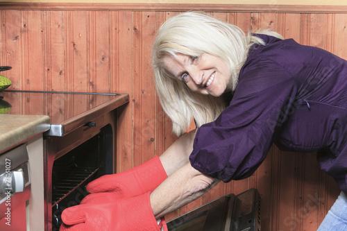 Leinwanddruck Bild senior woman baking cookies on the stove