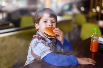 Little boy in fast food restaurant eat hamburger