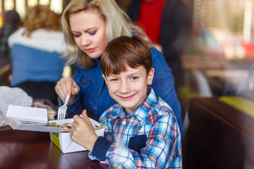 Little boy with mother in fast food restaurant