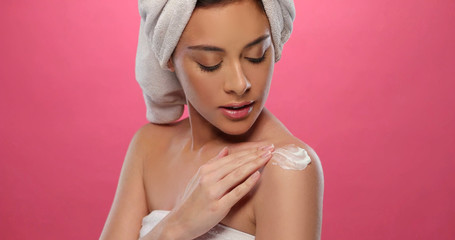 Peaceful brunette applying some cream on her arm