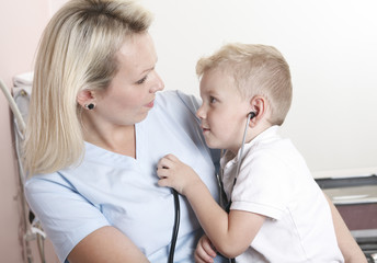 Female doctor using stethoscope to examining little sweet boy