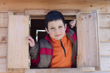 Child boy playing in wooden playhouse, looking from open window
