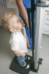 A young boy get measure in the hospital pediatrician