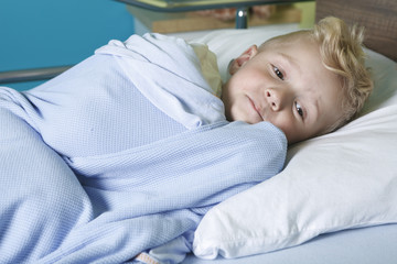 A sick little boy in a hospital bed