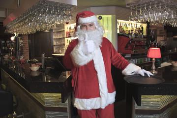 A Santa claus looking at camera in the bar