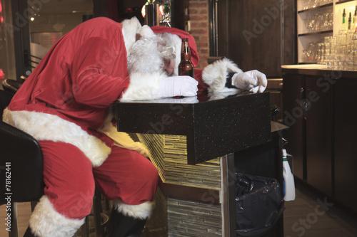 A Santa claus sleep at the bar. Too drunk. - 78162441