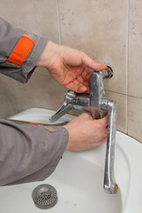 Plumber fixing faucet in a bathroom, replacing old tap