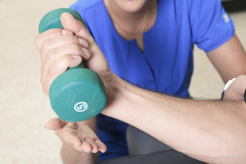 A men at the physio with a dumbell
