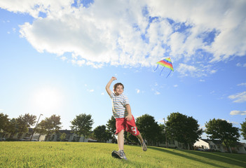 A Little boy running in park with a kite