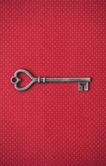 Old Metal Heart Shaped Key On Red Background