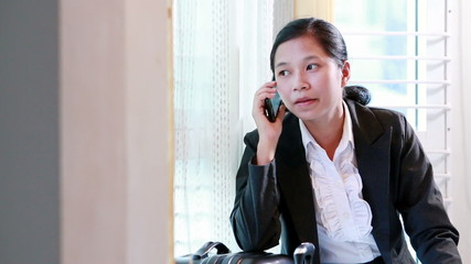 Business woman waiting for travel and calling a mobile phone.