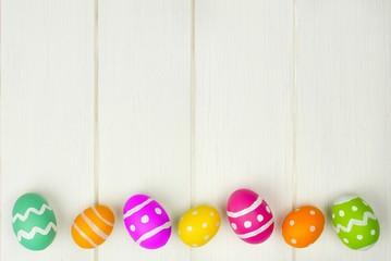 Colorful Easter egg bottom border against white wood