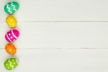 Colorful Easter egg side border against white wood