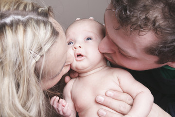 A beautiful couple with Baby on bed.