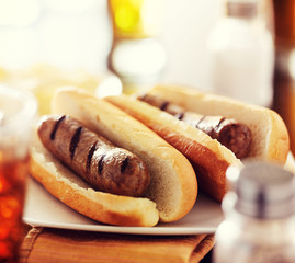 two juicey bratwursts on plate in hot dog buns