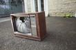 Leinwandbild Motiv An old broken TV left on the street.